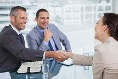 Cheerful young woman shaking hands with her future employer Royalty Free Stock Image