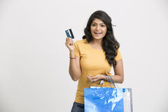 Cheerful Young woman with shopping bags and credit card. Cheerful Indian young woman with shopping bags and credit card on white Royalty Free Stock Photography