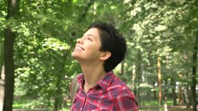 Cheerful young woman with short hair walking in park and smiling, beautiful green forest and shiny weather stock footage
