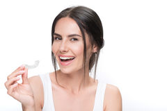 Cheerful young woman showing clear aligner. These orthodontic device will make my teeth perfect. Excited brunette girl is presenting clear-aligner treatment. She Royalty Free Stock Images