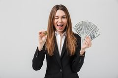 Cheerful young woman showing golden bitcoin and dollars in hands Royalty Free Stock Photos