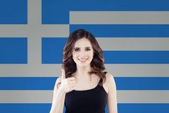 Cheerful young woman showing thumb up with Greece flag. Travel and learn greek language stock photos