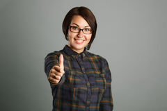 Cheerful young woman showing thumb up sign on grey background Stock Images