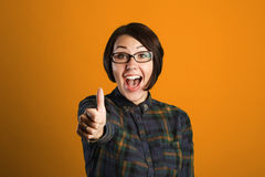 Cheerful young woman showing thumb up sign on orange background Royalty Free Stock Photo