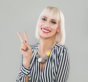 Cheerful young woman showing two fingers. Or victory gesture over grey background. Fashion model with bob haircut and makeup Stock Photo