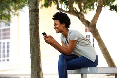 Cheerful young woman sitting on a bench reading text message Stock Photo