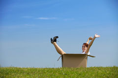 Cheerful young woman sitting in cardboard box at park with arms Royalty Free Stock Photos