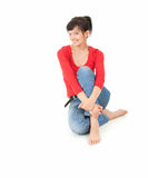 Cheerful young woman sitting on the floor Royalty Free Stock Image