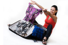 Lovely woman with her travel suitcase. Cheerful young woman sitting on the ground next to her open suitcase, taking out her summer clothes, looking at her dress Stock Photo