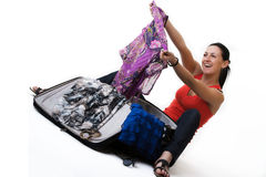 Happy travel woman unpacking her suitcase. Cheerful young woman sitting on the ground next to her open suitcase, taking out her summer clothes and rejoicing Royalty Free Stock Photography