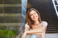 Cheerful young woman sitting outdoors and smiling. Portrait of cheerful young woman sitting outdoors and smiling Royalty Free Stock Photos