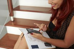 Female student testing friends. Cheerful young woman sitting on steps with textbook on her laps and texting friends from college royalty free stock photos