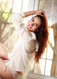 Cheerful young woman sitting on window sill Royalty Free Stock Photography