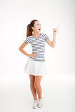 Cheerful young woman in skirt standing and pointing finger away. Cheerful excited young woman in skirt standing and pointing finger away over white background Royalty Free Stock Image