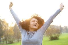 Cheerful young woman smiling with arms raised Stock Photo