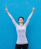 Cheerful young woman smiling with arms raised Stock Images