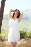 Cheerful young woman smiling in white dress in nature Stock Images