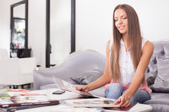 Cheerful young woman is spending time in salon Royalty Free Stock Photo