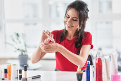 Cheerful young woman squeezing cream base on arm skin Royalty Free Stock Images