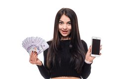Cheerful young woman standing isolated over white background looking camera holding money showing display of mobile phone. Image of cheerful young woman Royalty Free Stock Photo