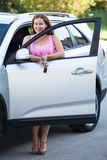 Cheerful young woman standing near vehicle with opened door Stock Photo