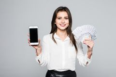 Cheerful young woman standing isolated over white background looking camera holding money showing display of phone. Cheerful young woman standing over white Royalty Free Stock Photo