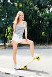 Cheerful young woman standing with skateboard Royalty Free Stock Images