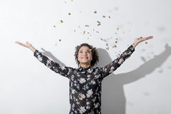 Cheerful young woman. Stretching out her hands while confetti falling on her Royalty Free Stock Photography