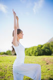 Cheerful young woman stretching outside. In a sunny meadow Royalty Free Stock Images