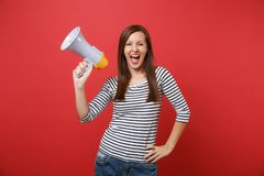 Cheerful young woman in striped clothes holding megaphone, keeping mouth wide open, screaming isolated on bright red. Wall background. People sincere emotions royalty free stock photography