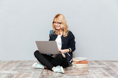 Cheerful young woman student using laptop computer. Picture of cheerful young woman student wearing glasses with backpack posing over grey wall. Looking aside Stock Photos