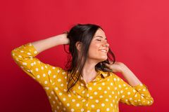 A cheerful young woman in studio on a red background, eyes closed. A cheerful young woman dressed in dotty yellow blouse, eyes closed. A studio shot on a red royalty free stock photo