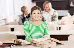 Cheerful young woman studying at desk with lots of Stock Images