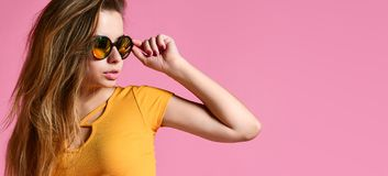 Cheerful young woman in sunglasses against pink background. stock image
