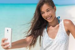 Asian woman fun beach selfie on summer vacation. Cheerful young woman taking fun mobile phone selfie photos of herself on beach holidays during summer tropical stock photography