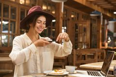 Cheerful young woman taking a picture of her lunch stock images
