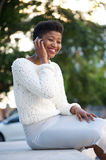 Cheerful young woman talking on cell phone outside Royalty Free Stock Photos