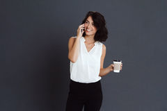 Cheerful young woman talking on her phone and holding coffee in hand Royalty Free Stock Photos