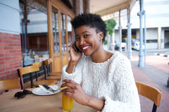 Cheerful young woman talking on mobile phone at cafe Stock Image