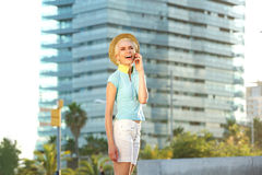 Cheerful young woman talking on mobile phone in the city Royalty Free Stock Images