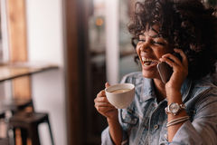 Cheerful young woman talking on phone in a cafe Stock Photos