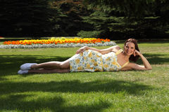 Cheerful young woman tanning in garden summer sun royalty free stock image