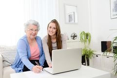 Cheerful young woman teaching computer to an old senior woman at home Royalty Free Stock Image