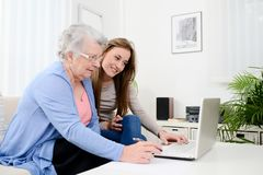 Cheerful young woman teaching computer to an old senior woman at home Stock Images
