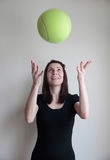 Cheerful young woman toss bаll. Cheerful young woman toss green bаll above head with hands isolated on grey Royalty Free Stock Photos