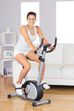 Cheerful young woman training on an exercise bike in her living room Stock Image