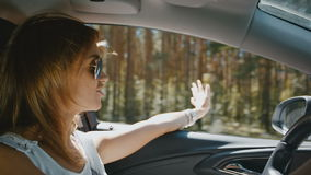 Cheerful young woman traveling by car. Cheerful young woman in sunglasses traveling by car stock video footage