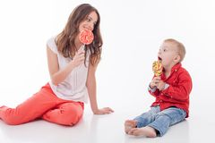 Cheerful young woman is treating her child. Beautiful mother and her little son are eating candy and sitting on flooring. The lady is smiling and looking at her stock photos