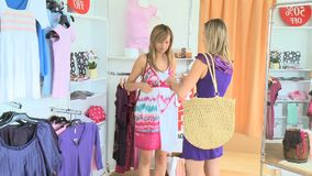 Cheerful young woman trying clothes. In a clothes store stock video