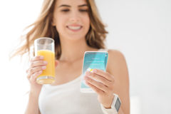 Cheerful young woman using cell phone. Always in touch . Positive emotional young beautiful woman drinking juice and using smart phone while expressing gladness royalty free stock photography
